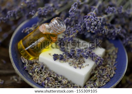 Bar of soap and lavender essence in a bowl - stock photo
