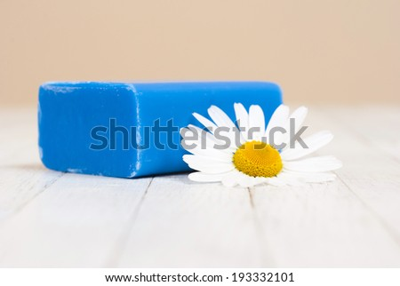 bar of soap with chamomile flower on white wood table