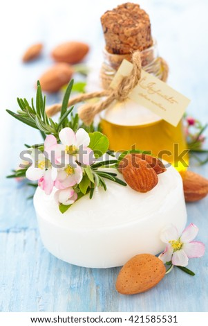 Bar of white soap with apple blossom, almonds and rosemary on old wooden table. - stock photo