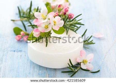 Bar of white soap with apple blossom and rosemary on old wooden table. - stock photo