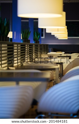 Bar or restaurant with empty tables and chairs in modern design - stock photo