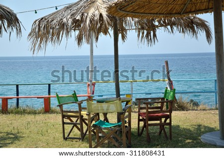 Bar tables and chairs under parasol with sea view