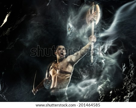 Barbarian. Strong man evokes the spirit of weapon - stock photo