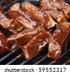 barbecue beef spare ribs cooking on a grill outdoors in summer - stock photo