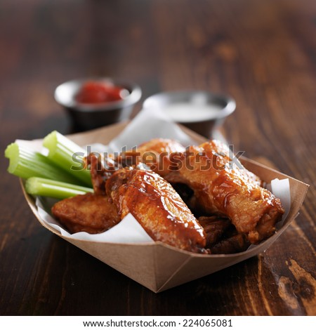 barbecue buffalo chicken wings with celery sticks and ranch sauce in basket - stock photo