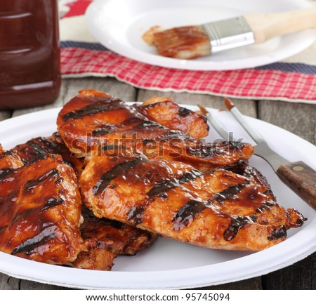 Barbecue chicken breast on a paper plate - stock photo