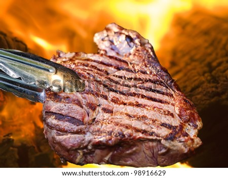 Barbecue concept with a juicy steak in front of a roaring grill fire.