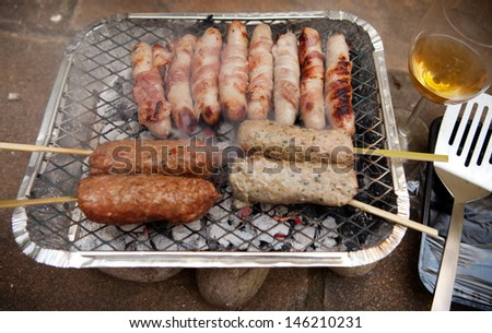 barbecue frying sausages and shish kebab. disposable bbq with meat skewer cooking on hot coals - stock photo