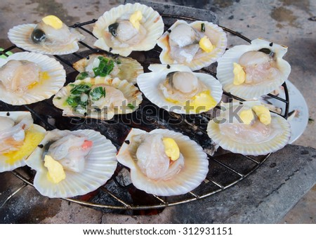 Barbecue grill cooking seafood, grilling scallops with butter onion and nuts