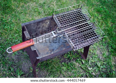 Barbecue grill on a background of green grass. - stock photo