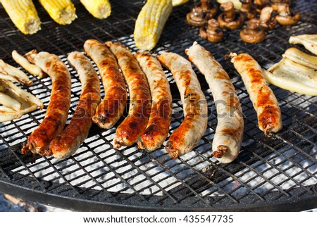 Barbecue grill outdoors. Cookout german bbq food. Big roasted pork and beef sausages. Meat grilled snack. Street food, fast food. Tasty appetizer, sausages. - stock photo