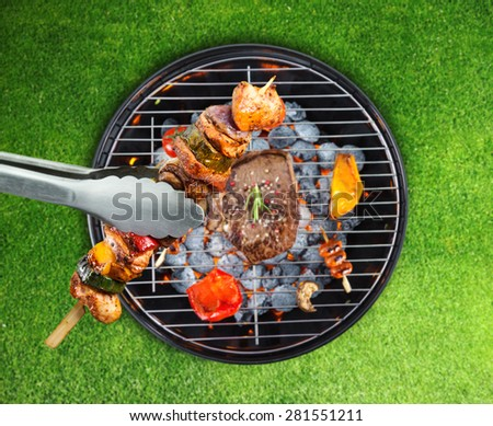 Barbecue grill with various kinds of meat. Placed on grass - stock photo