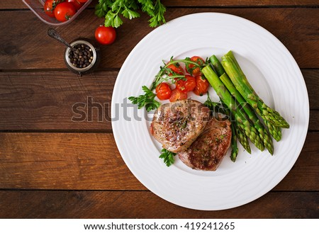 Barbecue grilled beef steak meat with asparagus and tomatoes. Top view - stock photo