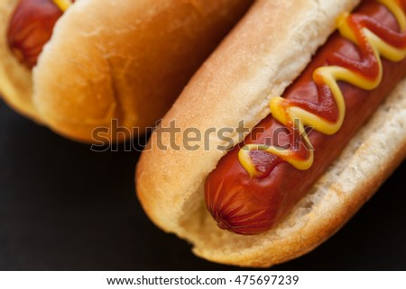 Barbecue Grilled Hot Dog with Yellow Mustard and ketchup on black background