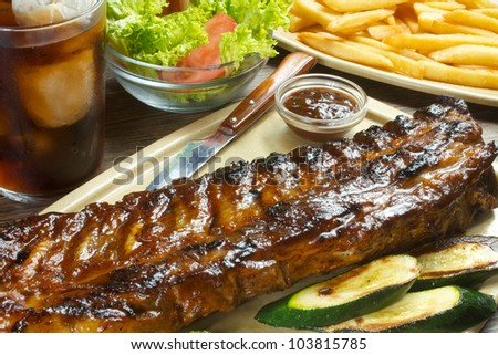 barbecue grilled ribs with bbq sauce, fries and salad - stock photo