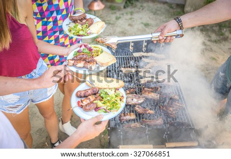 Barbecue in home garden, Host serving his guests - Group of friends making barbecue and having fun at private party - stock photo