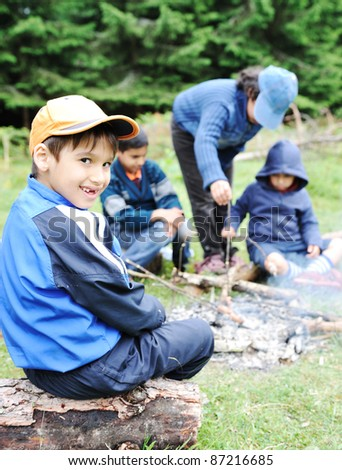Barbecue in nature, group of children  preparing sausages on fire - stock photo