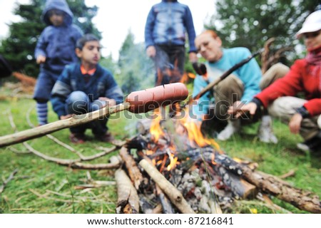 Barbecue in nature, group of people preparing sausages on fire (note: selected focus) - stock photo
