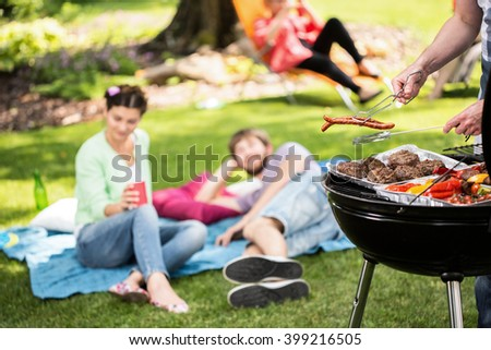 Barbecue in park with friends on a sunny afternoon - stock photo