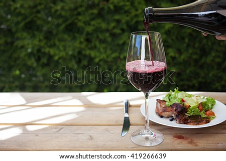 Barbecue meat served with red souse and green mixed salad. Pouring wine into glass.