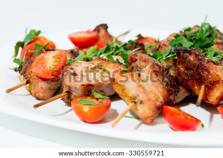 Barbecue on skewers, garnished with cherry om white plate
