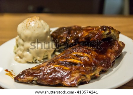 barbecue pork spareribs. Closeup of barbecued pork ribs and vegetables. Close up Gourmet Grilled Pork Rib and Smashed Potato Wedges on White Plate with Sauce and Veggies - stock photo