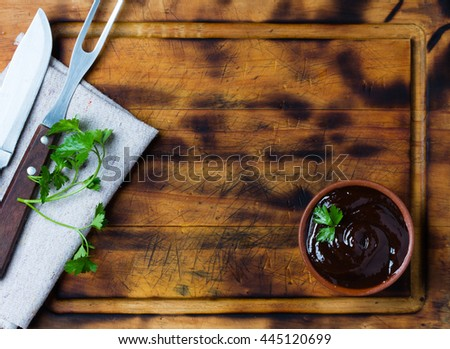 Barbecue sauce in clay bowl, meat fork and knife and napkin on wooden cutting board. - stock photo