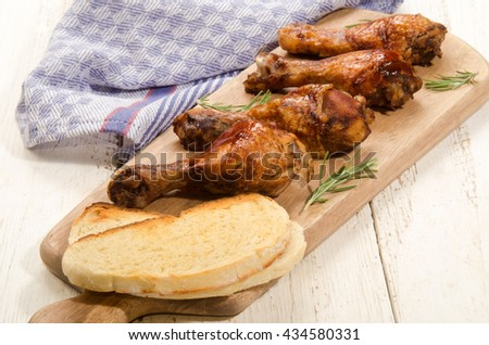 barbecue sauce marinated chicken drumsticks with toasted bread on wooden board   - stock photo
