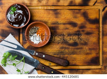 Barbecue sauce, salt, red and black pepper in clay bowls, meat fork, knife and napkin on wooden cutting board. Top view. Copy space - stock photo