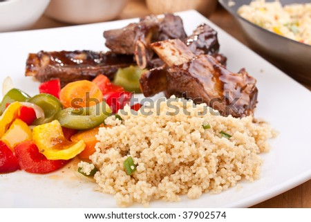 ... spare ribs on a plate with vegetables and couscous - stock