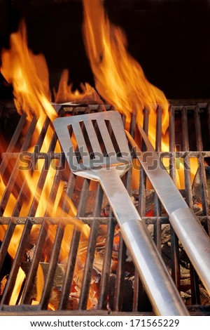 Barbecue Utensils on Hot Grill. You can see more BBQ, grilled food, flames and fire on my page.   - stock photo