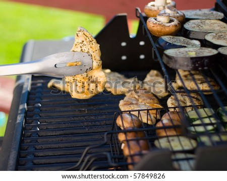 Barbecued chicken being flipped on an outdoor grill