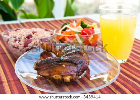Barbecued chicken leg also known as Jerk Chicken - Caribbean style served with vegetables, rice and lemonade.  Shallow DOF. - stock photo