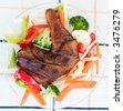 Barbecued chicken leg also known as Jerk Chicken - Caribbean style served with vegetables.  Shallow DOF. - stock photo