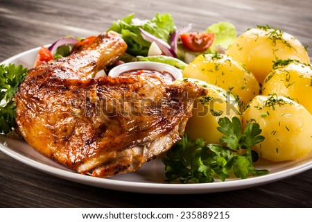 Barbecued chicken leg with boiled potatoes and vegetables - stock photo