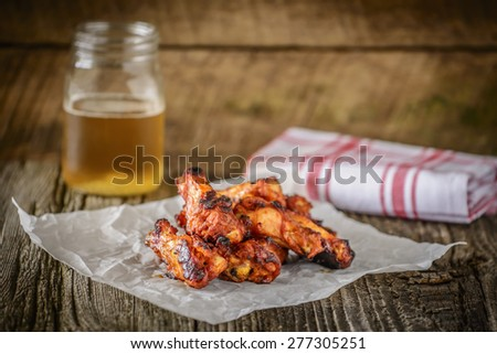 Barbecued chicken wings photographed on a rustic background. - stock photo