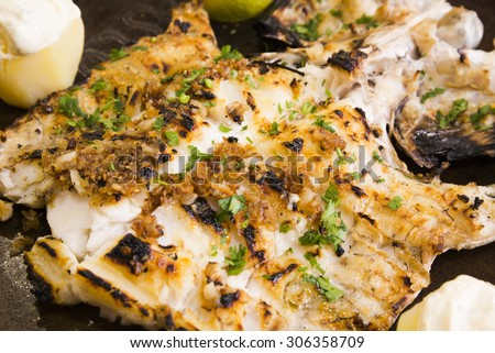 Barbecued hake tail with toasted garlic - stock photo