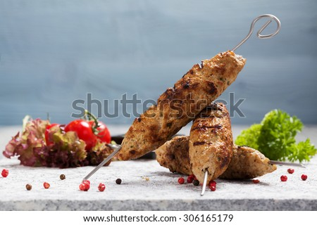 Barbecued kofta - kebeb with vegetables on a plate. Selective focus - stock photo