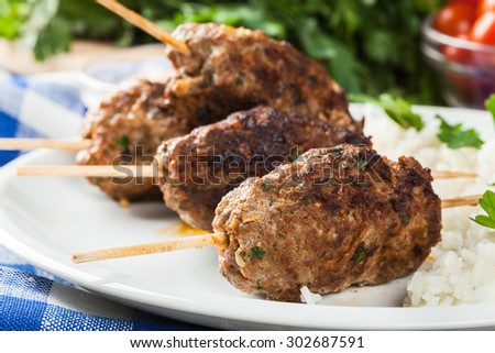 Barbecued kofta with rice on a plate. Selective focus