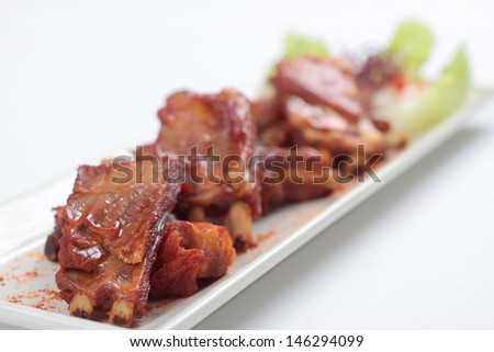 Barbecued lamb ribs on white plate