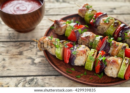 Barbecued marinated turkey or chicken meat shish kebab skewers with ketchup sauce, chopped parsley and tomatoes on rustic wooden table background. Traditional barbecue grill food - stock photo
