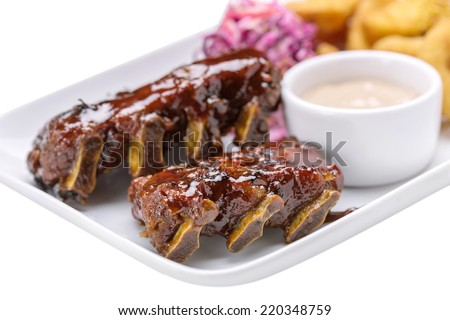 Barbecued pork ribs served with potatoes, corn and mushroom sauce isolated on white background - stock photo