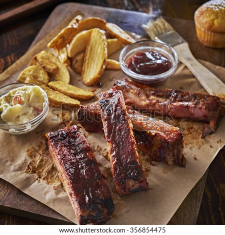 barbecued pork spare ribs with fried potato wedges and cole slaw on parchment paper. - stock photo