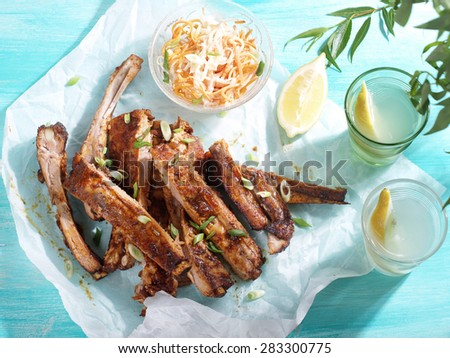 Barbecued ribs in a spicy marinade with salad, selective focus - stock photo