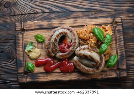 Barbecued sausages and braised cabbage on a rustic serving board
