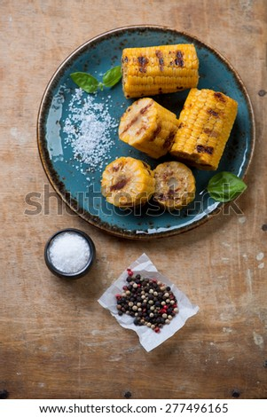 Barbecued sweetcorn with sea salt and pepper, view from above - stock photo