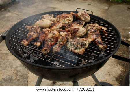 barbecuing chicken drumsticks marinated in herbs - stock photo