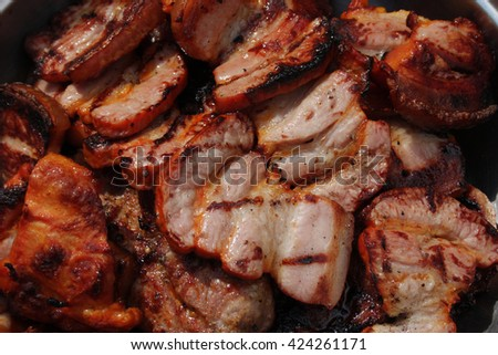 Barbecuing meat on charcoal fire closeup image.