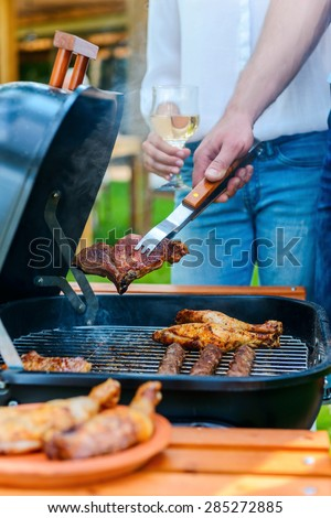Barbecuing meat on grill. Close-up of two people barbecuing meat on the grill while standing outdoors