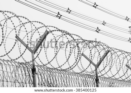 Barbed Razor Wire Fence - black and white - stock photo
